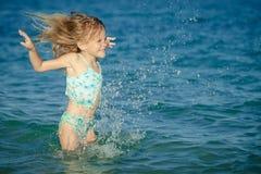 Latająca doskakiwanie plaży dziewczyna przy błękitnym dennym brzeg fotografia royalty free
