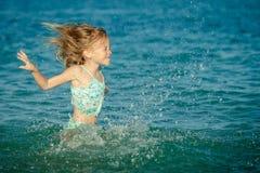 Latająca doskakiwanie plaży dziewczyna przy błękitnym dennym brzeg zdjęcia royalty free