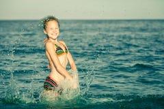 Latająca doskakiwanie plaży dziewczyna przy błękitnym dennym brzeg fotografia stock