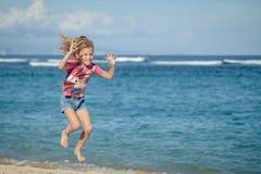 Latająca doskakiwanie plaży dziewczyna przy błękitnym dennym brzeg ja zdjęcia stock