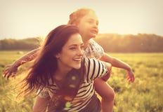 Latająca dzieciak dziewczyna śmia się na szczęśliwej cieszy się matce na su z powrotem zdjęcie stock