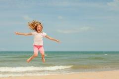 Latającego skoku plaży dziewczyna na błękitnym dennym brzeg zdjęcia stock