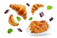 Latający croissants z czekoladowymi i nowymi liśćmi odizolowywającymi Zdjęcie Royalty Free