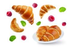 Latający croissants z malinkami i nowymi liśćmi odizolowywającymi Zdjęcia Stock
