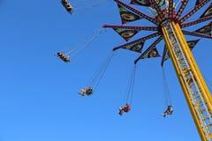 Latający huśtawkowy carousel przeciw niebieskiemu niebu Zdjęcia Royalty Free