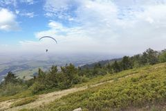 Latający paraglider przeciw niebieskiemu niebu w ranek mgle Karpackie góry, obrazy stock