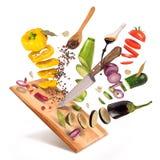 Latający plasterki pokrojeni warzywa słuzyć na drewnianej desce Fotografia Royalty Free