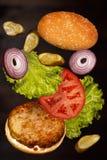 Latający składniki świeży smakowity hamburger Zdjęcia Royalty Free