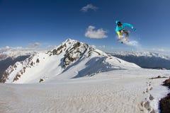 Latający snowboarder na górach, krańcowy sport Zdjęcie Royalty Free
