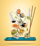 Latający suszi kawałki słuzyć na talerzu, oddzielającym na barwionym backgr Zdjęcie Stock