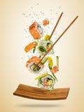 Latający suszi kawałki słuzyć na talerzu, oddzielającym na barwionym backgr Obraz Royalty Free