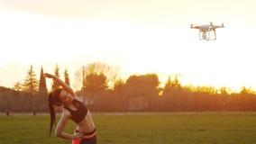 Latający truteń z kamera krótkopędów sprawności fizycznej dziewczyną robi stronie zgina zbiory