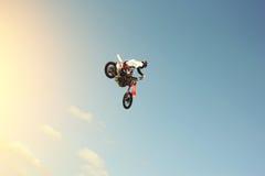 Latający motobiker na niebieskiego nieba tle Zdjęcie Stock