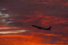 Latający samolot na tle kolorowy zmierzch Zdjęcia Stock