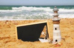 Latarnia morska, żaglówka i chalkboard, na dennym piasku i oceanu horyzoncie Obrazy Stock