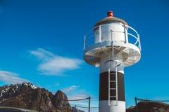Latarnia morska na molu na tle góry i niebieskie niebo na Lofoten wyspach obrazy royalty free