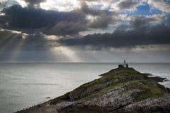 Latarnia morska na przylądkowym z słońcem promienieje nad oceanu krajobrazem z fotografia stock