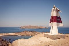 latarnia morska nad śpiczastym rockowym morzem Fotografia Royalty Free