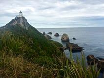 Latarnia morska przegapia Skalistą Niewygładzoną linię brzegową na plażach Południowy Nowa Zelandia obraz stock