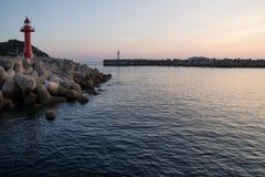 Latarnie morskie podczas świtu przy nadmorski z wavebreakers w Seogwipo, Jeju wyspa, Południowy Korea Fotografia Stock