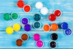 Latas abertas misturadas da pintura em um fundo de madeira azul Fotografia de Stock