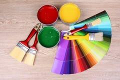 Latas abiertas con colores brillantes, los cepillos y la gama de colores Imagenes de archivo