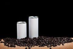 Latas blancas con los granos de café Fotografía de archivo