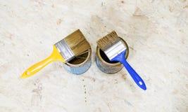 Latas da pintura e da escova no azul e no amarelo Fotos de Stock
