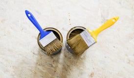 Latas da pintura e da escova no azul e no amarelo Imagem de Stock