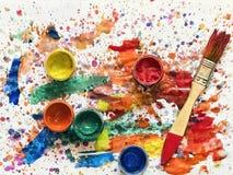 Latas da pintura e de uma escova em uma folha coberta na pintura Foto de Stock Royalty Free