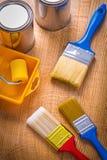 Latas das escovas de pintura do rolo da bandeja na placa de madeira Fotos de Stock Royalty Free