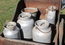 latas de aluminio viejas de la leche al transporte de la leche fresca en una c de madera Imagen de archivo libre de regalías