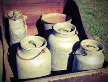 latas de aluminio viejas de la leche al transporte de la leche fresca en una c de madera Imágenes de archivo libres de regalías