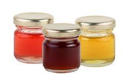 3 latas de atascos multicolores y de miel aislados en el fondo blanco Imagen de archivo libre de regalías
