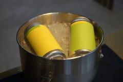 Latas de bebida amarillas en cubo de hielo fotos de archivo libres de regalías