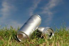 Latas de cerveza en la hierba Imágenes de archivo libres de regalías