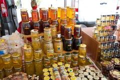 Latas de cristal con diversos tipos de miel Fotos de archivo libres de regalías