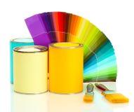 Latas de estaño con la pintura, los cepillos y la gama de colores brillante Foto de archivo