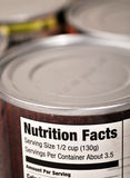 Latas de estaño del alimento con la escritura de la etiqueta de los hechos de la nutrición Fotos de archivo libres de regalías