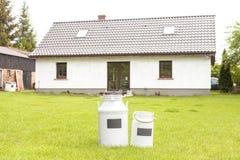 Latas de la leche delante de una casa fotos de archivo libres de regalías
