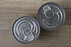 Latas de lata para o alimento no fundo de madeira fotografia de stock royalty free