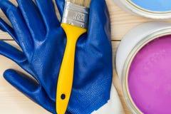 Latas de pintura de hogar, de un cepillo y de pares de guantes Imagenes de archivo