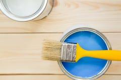 Latas de pintura de hogar y de una brocha Imagen de archivo libre de regalías