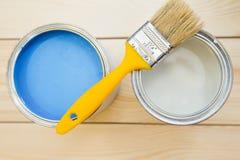 Latas de pintura de hogar y de una brocha Imágenes de archivo libres de regalías
