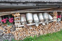 Latas e lenha velhas do leite na cabana alpina Imagens de Stock