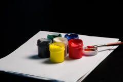 Latas multicoloras de aguazo con la brocha foto de archivo