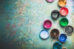 Latas multicoloras de la pintura en fondo de madera Fotos de archivo
