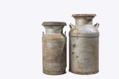 Latas oxidadas viejas de la leche aisladas en blanco Imagenes de archivo