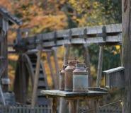 Latas viejas de la leche en una tabla, molino de agua en el fondo, otoño Foto de archivo