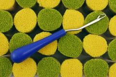 Latch Hook Rug Making Supplies. Latch hook rug crafting tool atop bundles of rug yarn Royalty Free Stock Images